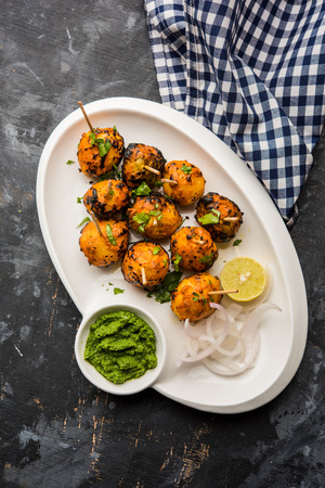 Tandoori aloo are roasted potatoes with Indian spices. It's a party appetizer served with green chutney. selective focus Imagens