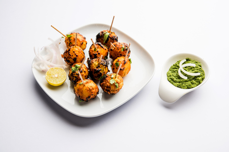 Tandoori aloo are roasted potatoes with Indian spices. It's a party appetizer served with green chutney. selective focus