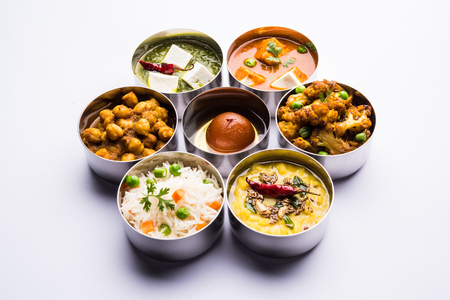 assorted Indian/Pakistani food in stainless steel bowls creating pattern or design, selective focus Imagens