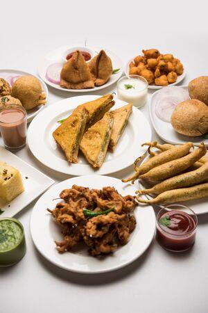 Indian Tea time snacks  in group includes Veg Samosa, Kachorikachaudi, aloo bonda, khaman dhokla, bread, onion,chilli and moong pakorapakodabhajibhajjiBhajiyabajji with sauces, selective focus