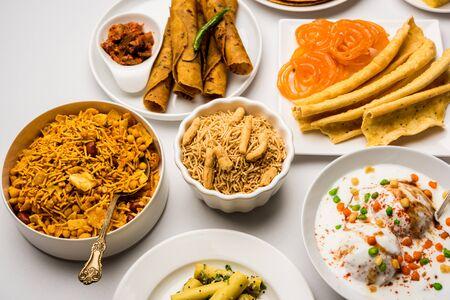 Group of Gujarati snacks like jalebi-fafda, thepla, khaman dhokla, aloo bhujiya, khandvi,khakra, dahi vada, gathiya with hot tea Stock Photo