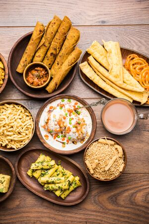 Group of Gujarati snacks like jalebi-fafda, thepla, khaman dhokla, aloo bhujiya, khandvi,khakra, dahi vada, gathiya with hot tea Reklamní fotografie