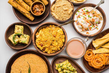 Group of Gujarati snacks like jalebi-fafda, thepla, khaman dhokla, aloo bhujiya, khandvi,khakra, dahi vada, gathiya with hot tea 写真素材