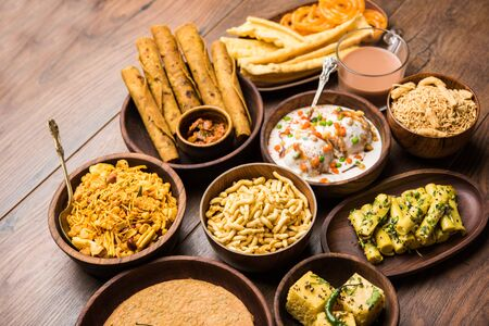 Gruppe von Gujarati-Snacks wie Jalebi-Fafda, Thepla, Khaman Dhokla, Aloo Bhujiya, Khandvi, Khakra, Dahi Vada, Gathiya mit heißem Tee Standard-Bild