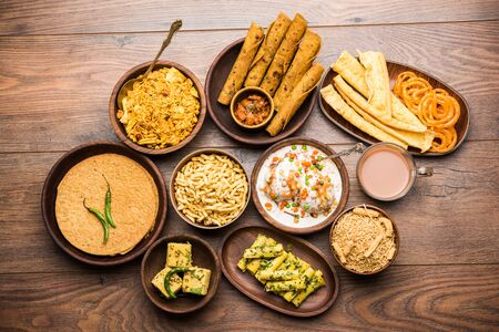 Group of Gujarati snacks like jalebi-fafda, thepla, khaman dhokla, aloo bhujiya, khandvi,khakra, dahi vada, gathiya with hot tea Фото со стока