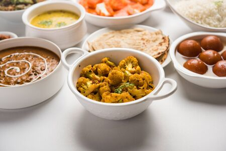 Assorted Indian food like paneer butter masala, dal, roti, rice, sabji, gulab jamun and bound raita served in bowls over moody background, selective focus Stock Photo - 125859407