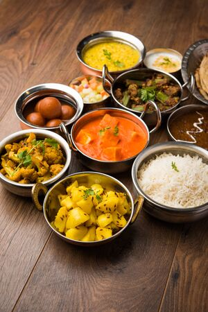 Assorted Indian food like paneer butter masala, dal, roti, rice, sabji, gulab jamun and bound raita served in bowls over moody background, selective focus Stock Photo - 125859444