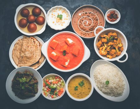 Assorted Indian food like paneer butter masala, dal, roti, rice, sabji, gulab jamun and bound raita served in bowls over moody background, selective focus Stock Photo - 125859452
