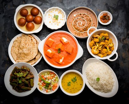 Assorted Indian food like paneer butter masala, dal, roti, rice, sabji, gulab jamun and bound raita served in bowls over moody background, selective focus Stock Photo