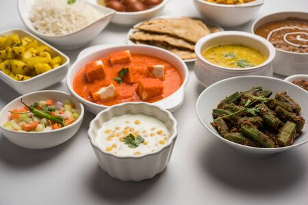 Assorted Indian food like paneer butter masala, dal, roti, rice, sabji, gulab jamun and bound raita served in bowls over moody background, selective focus Stock Photo - 125859469