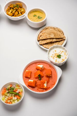 Assorted Indian food like paneer butter masala, dal, roti, rice, sabji, gulab jamun and bound raita served in bowls over moody background, selective focus Stock Photo - 125859471