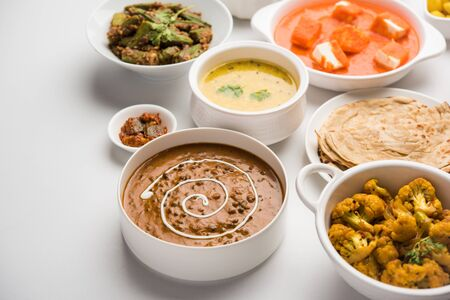Assorted Indian food like paneer butter masala, dal, roti, rice, sabji, gulab jamun and bound raita served in bowls over moody background, selective focus Stock Photo - 125859474