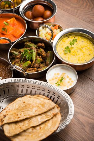 Assorted Indian food like paneer butter masala, dal, roti, rice, sabji, gulab jamun and bound raita served in bowls over moody background, selective focus Stock Photo - 125859476