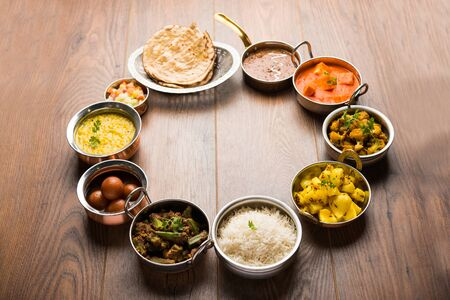 Assorted Indian food like paneer butter masala, dal, roti, rice, sabji, gulab jamun and bound raita served in bowls over moody background, selective focus Stock Photo - 125859506