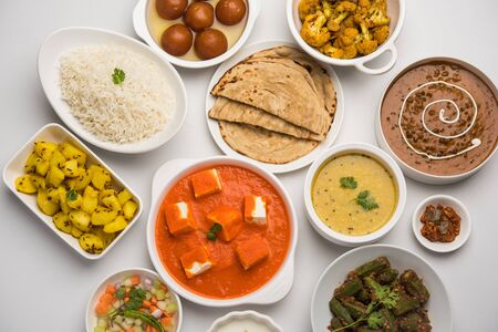 Assorted Indian food like paneer butter masala, dal, roti, rice, sabji, gulab jamun and bound raita served in bowls over moody background, selective focus Stock Photo - 125859558