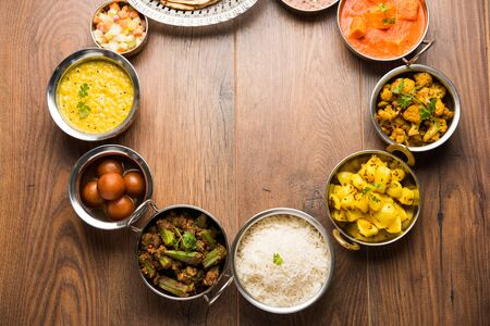 Assorted Indian food like paneer butter masala, dal, roti, rice, sabji, gulab jamun and bound raita served in bowls over moody background, selective focus Stock Photo - 125859596
