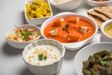 Assorted Indian food like paneer butter masala, dal, roti, rice, sabji, gulab jamun and bound raita served in bowls over moody background, selective focus Stock Photo - 125859627