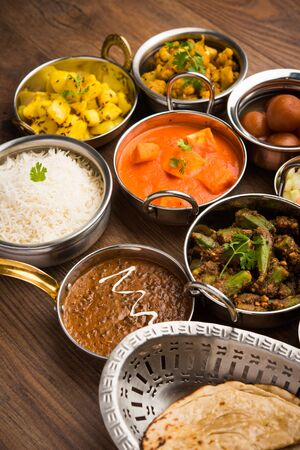 Assorted Indian food like paneer butter masala, dal, roti, rice, sabji, gulab jamun and bound raita served in bowls over moody background, selective focus Stock Photo - 125859633