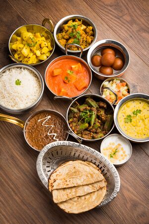 Assorted Indian food like paneer butter masala, dal, roti, rice, sabji, gulab jamun and bound raita served in bowls over moody background, selective focus Stock Photo - 125859654