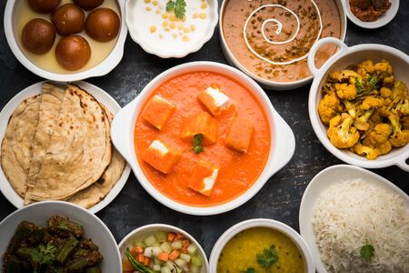 Assorted Indian food like paneer butter masala, dal, roti, rice, sabji, gulab jamun and bound raita served in bowls over moody background, selective focus Stock Photo - 125859724