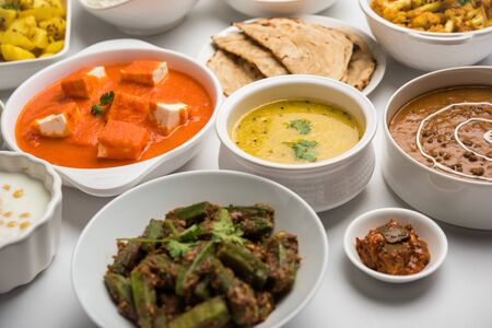 Assorted Indian food like paneer butter masala, dal, roti, rice, sabji, gulab jamun and bound raita served in bowls over moody background, selective focus Stock Photo - 125859772