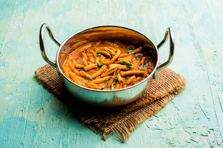 Dhaba style Sev bhajisabzicurry made in tomato curry with gathiya shev, served in kerahi, selective focus