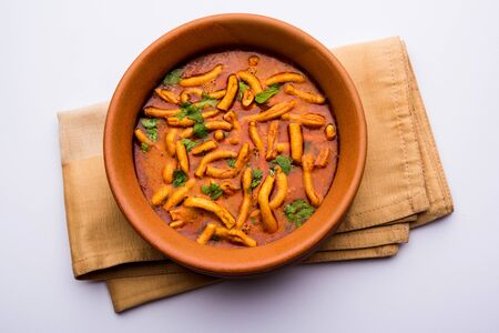Dhaba style Sev bhajisabzicurry made in tomato curry with gathiya shev, served in a bowl, selective focus