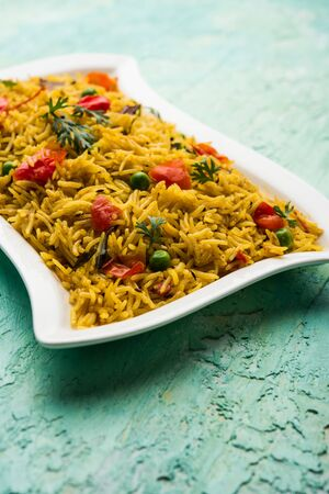 Tomato Pulav or Pilaf made using basmati rice and red tomatoes, served in a bowl. selective focus