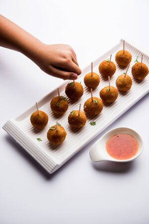 Crispy Veg lollipop recipe made using boiled potato with spices covered with corn flour and bread crumbs coating and then deep fried, served with toothpick or ice cream stock inserted in it with sauce Stock Photo