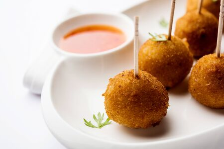 Crispy Veg lollipop recipe made using boiled potato with spices covered with corn flour and bread crumbs coating and then deep fried, served with toothpick or ice cream stock inserted in it with sauce