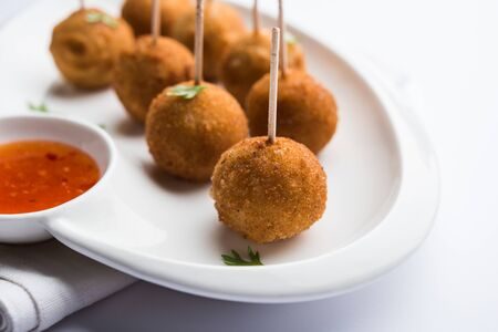 Crispy Veg lollipop recipe made using boiled potato with spices covered with corn flour and bread crumbs coating and then deep fried, served with toothpick or ice cream stock inserted in it with sauce Reklamní fotografie