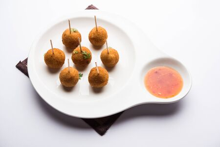 Crispy Veg lollipop recipe made using boiled potato with spices covered with corn flour and bread crumbs coating and then deep fried, served with toothpick or ice cream stock inserted in it with sauce 스톡 콘텐츠