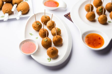 Crispy Veg lollipop recipe made using boiled potato with spices covered with corn flour and bread crumbs coating and then deep fried, served with toothpick or ice cream stock inserted in it with sauce 免版税图像