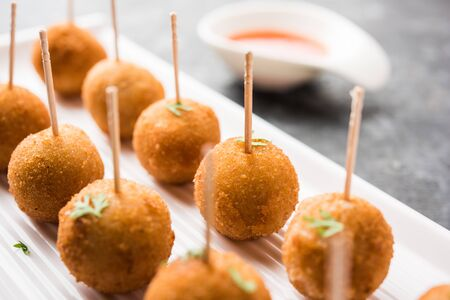 Crispy Veg lollipop recipe made using boiled potato with spices covered with corn flour and bread crumbs coating and then deep fried, served with toothpick or ice cream stock inserted in it with sauce 写真素材