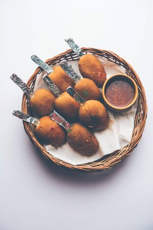 Crispy Veg lollipop recipe made using boiled potato with spices covered with corn flour and bread crumbs coating and then deep fried, served with toothpick or ice cream stock inserted in it with sauce Imagens