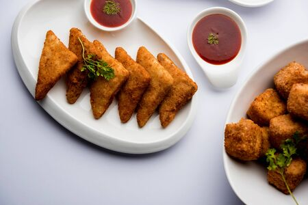 Crispy Paneer popcorn, potato triangles and Maggie/noodles pakora or pakoda, served in white bowl and plate over white background