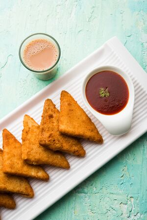 crispy Potato triangles or batata vada covered with bread crumbs and then deep fried. served with tomato ketchup. selective focus