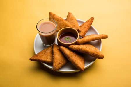 crispy Potato triangles or batata vada covered with bread crumbs and then deep fried. served with tomato ketchup. selective focus Banco de Imagens