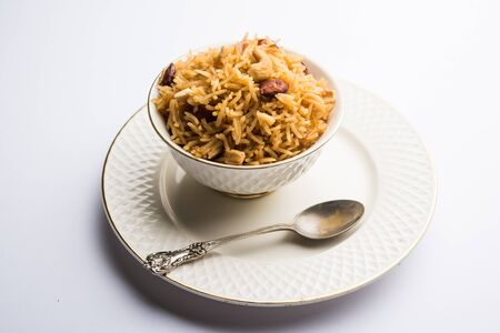 Traditional Jaggery Rice or Gur wale chawal in Hindi, served in a bowl with spoon. selective focus