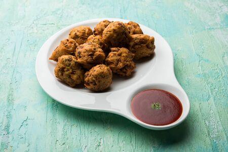 rava Bhajj or bhajiya also known as suji Pakoda or semolina Pakora, served with tomato ketchup. selective focus