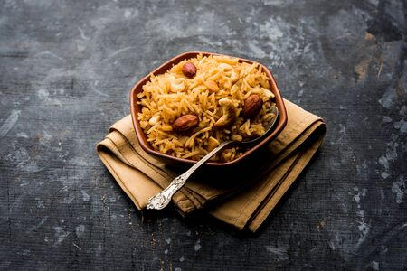 Traditional Jaggery Rice or Gur wale chawal in Hindi, served in a bowl with spoon. selective focus Stock Photo