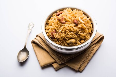 Traditional Jaggery Rice or Gur wale chawal in Hindi, served in a bowl with spoon. selective focus Imagens