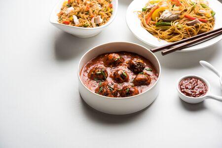 Un assortiment de plats indo-chinois en groupe comprend des nouilles hakka schezwan/szechuan non végétariennes ou au poulet, du riz frit, de la manchourie, des œufs chop suey américains, de la soupe avec une cuillère et des baguettes, mise au point sélective