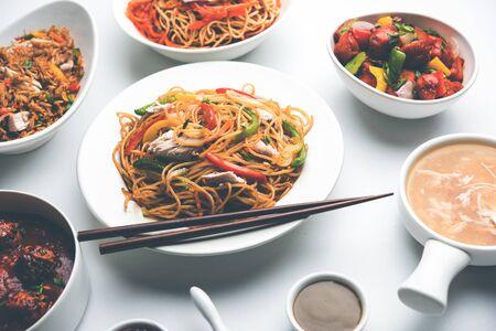 Il cibo indo cinese assortito in gruppo include spaghetti Schezwan/Szechuan hakka non vegetariani o di pollo, riso fritto, manciuria, uovo americano chop suey, zuppa con cucchiaio e bastoncini, messa a fuoco selettiva