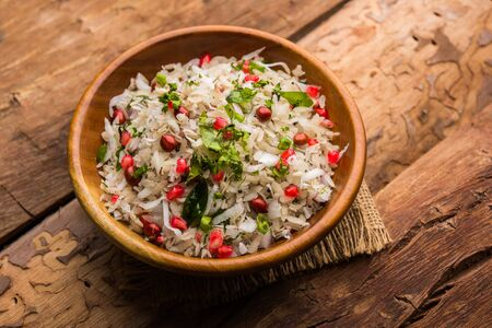 Dapde Pohe is a typical Maharashtrian breakfast, made with thin variety of poha and fresh coconut with chili, peanuts and nuts. served in a bowl or plate.