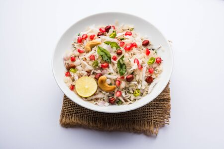 Dapde Pohe is a typical Maharashtrian breakfast, made with thin variety of poha and fresh coconut with chili, peanuts and nuts. served in a bowl or plate. Banque d'images