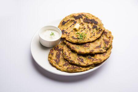 Thalipeeth es un tipo de panqueque sabroso de múltiples granos popular en Maharashtra, India, servido con cuajada / mantequilla o ghee Foto de archivo