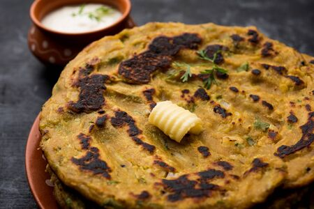 Thalipeeth is a type of savoury multi-grain pancake popular in Maharashtra, India served with curd/butter or ghee Banco de Imagens