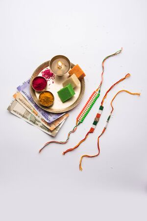 Tricolour Rakhi and Sweets for Independence Day / Raksha Bandhan which is on the Same Day in 2019, puja thali decorated with diya, haldi/kumkum and indian currency as gift Stock Photo