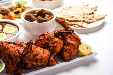 Receta variada de comida india no vegetariana servida en grupo. Incluye pollo al curry, cordero masala, anda / huevo al curry, pollo con mantequilla, biryani, tandoori murgh, pollo-tikka y naan / roti Foto de archivo